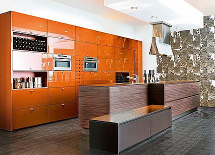 Küche mit orangen Hochglanzfronten von KH System Möbel